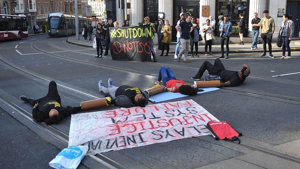 Demonstranter ligger fastkedjade utanför Notthinghams Kungliga Teater för att stoppa buss och spårvagnstrafik in i stadskärnan.
