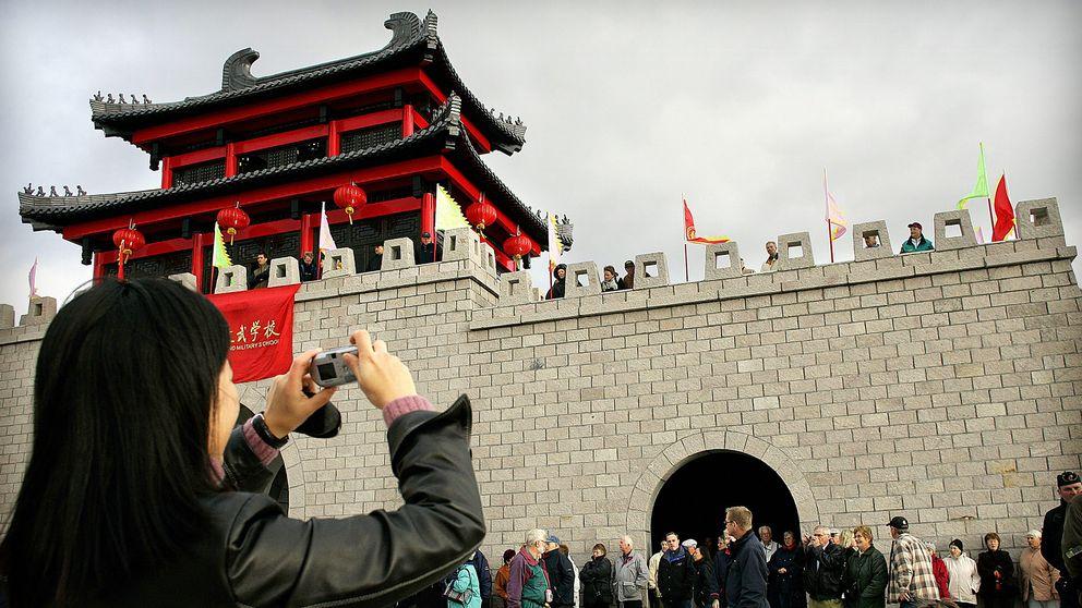 Kvinna fotograferar Dragon Gate