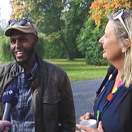 yngre man och medelålders kvinna intervjuas utomhus, båda glada och ler