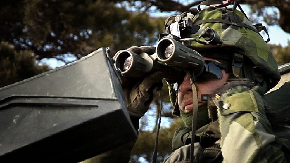 Soldat tittar i kikare.