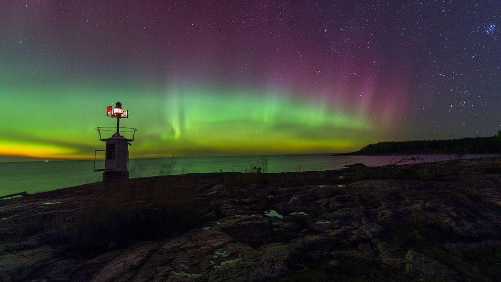 En liten fyr och klipphällar i förgrunden. Ovan havet syns gulgrönt norrsken mot lilablå stjärnhimmel.