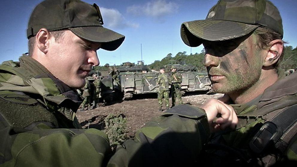Soldater fixar krigsmask inför övning på Tofta skjutfält.