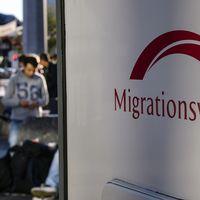 Migranter och Migrationsverket-skylt.
