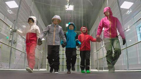 Fyra barn i regnkläder går på löpband inuti en regn- och vindsimulator. Det regnar på dem.