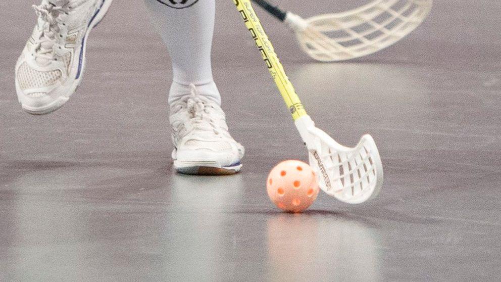 En bild av ett par fötter, en innebandyklubba och en innebandyboll.