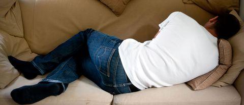 En man som ligger på en soffa och vilar.