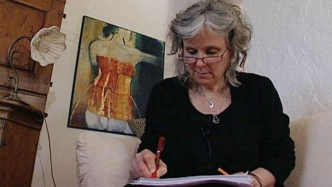 Birgitta Lillpers sitter i en soffa, antecknar