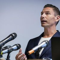 Elias står framför ett par mikrofoner på en presskonferens.