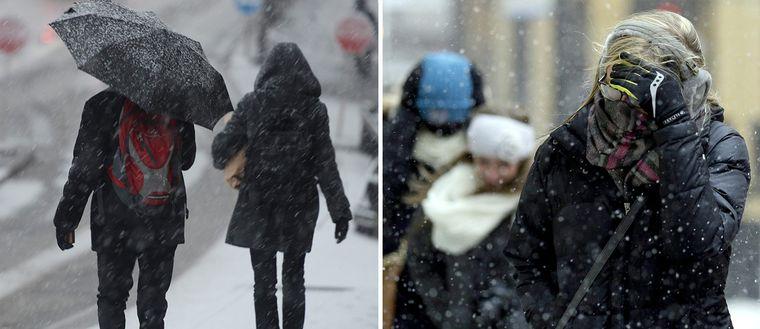 Personer som går i snöoväder.