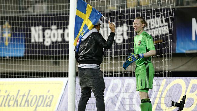 En man med en svenskflagga står vid den svenska målvakten.