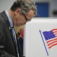 En man vid ett valbås med en amerikansk flagga.