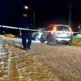 En bild med poliser, polisbilar kring brottsplatsen som är avspärrad.