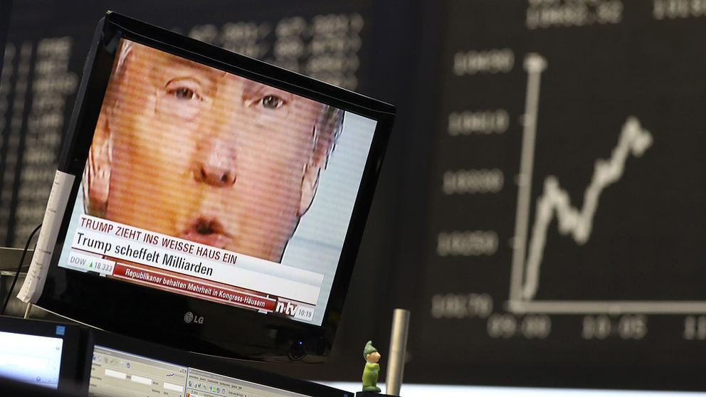 A TV screen showing U.S. President-elect Donald Trump is pictured in front of the German share price index, DAX board, at the stock exchange in Frankfurt, Germany, November 9, 2016. REUTERS/Staff/Remote