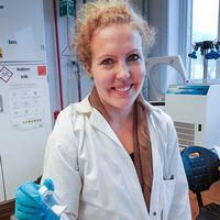 Porträtt på Sara Frykstrand doktor teknisk fysik. Hon håller en bruk med Upsalite i handen. Har en vit labbrock och blå vinylhandskat på sig. Står i labbmiljö.