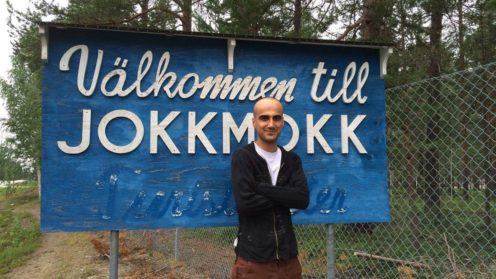 """Man framför skylt med texten """"Välkommen till Jokkmokk"""""""