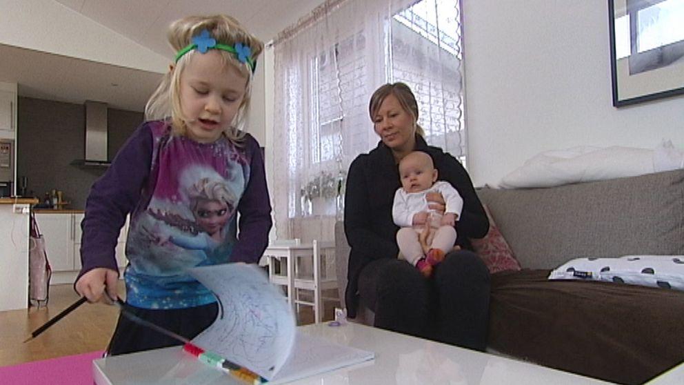 Ester bläddrar i ett ritblock, medan mamma Kristina sitter i soffan med lillasyster Julie i knät.