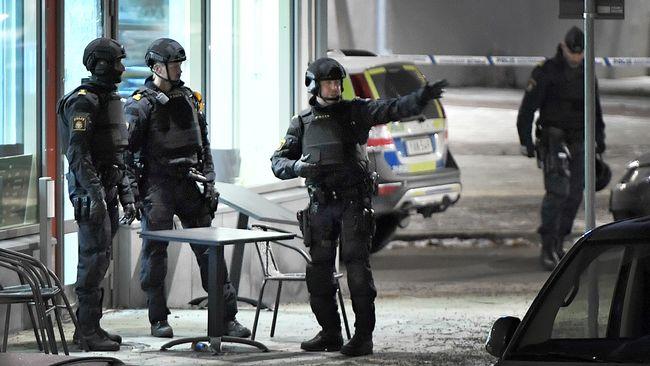 Polis utrustad med skyddsvästar och hjälmar utanför det kafé där skottlossningen ägde rum under fredagskvällen.