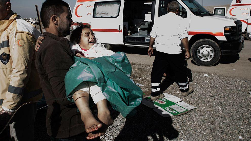 En pappa springer med sin dotter till ambulansen som ska ta henne vidare till Erbil och bättre sjukvård