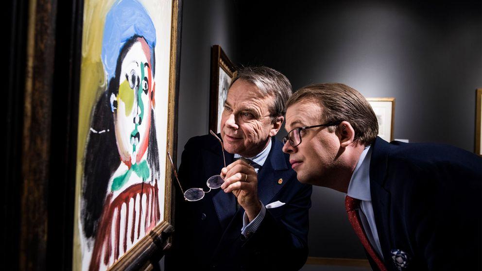 Till vänster i bild hänger en målning på en vägg. Två män betraktar bilden på nära avstånd. Mannen närmast tavlan håller sina glasögon i handen.