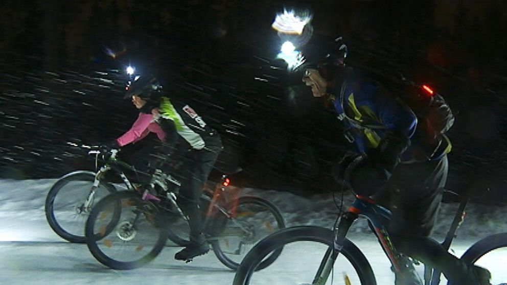 Tre cyklister med pannlampor stretar i ymnigt snöfall