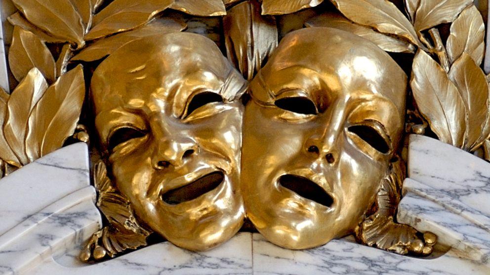 teatermasker i guld som utsmyckning på vägg