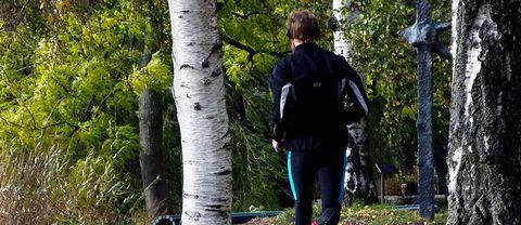 Joggande man med hörlurar i björkskog.