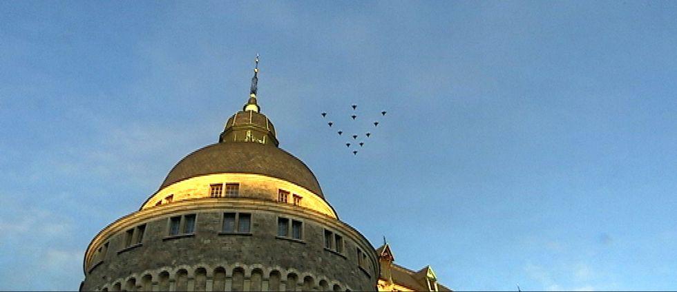 JAS-plan i formation av en julgran, på bilden uppochnedvänd, flyger över Örebro slott.