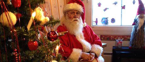 Värmlandstomten sitter vid en julgran.