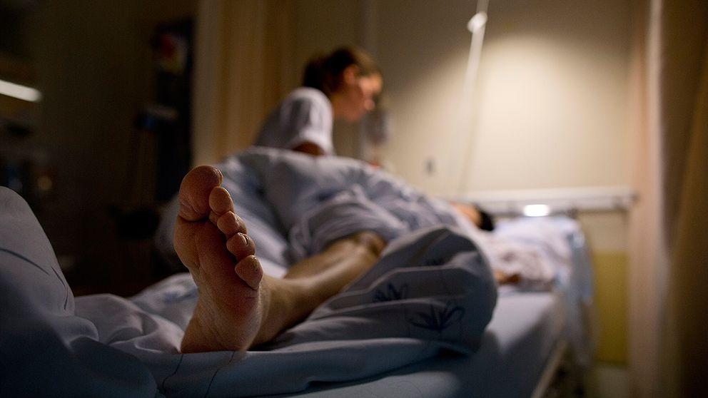 Sjuksköterska ser till en patient i en sjukhussäng.