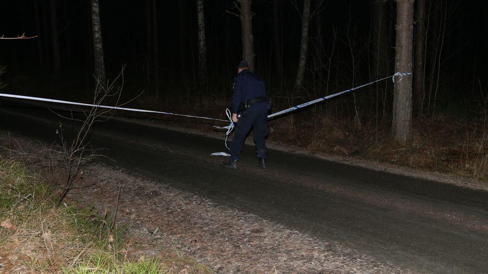 En polis som sätter upp ett avspärrningsband på en liten grusväg.