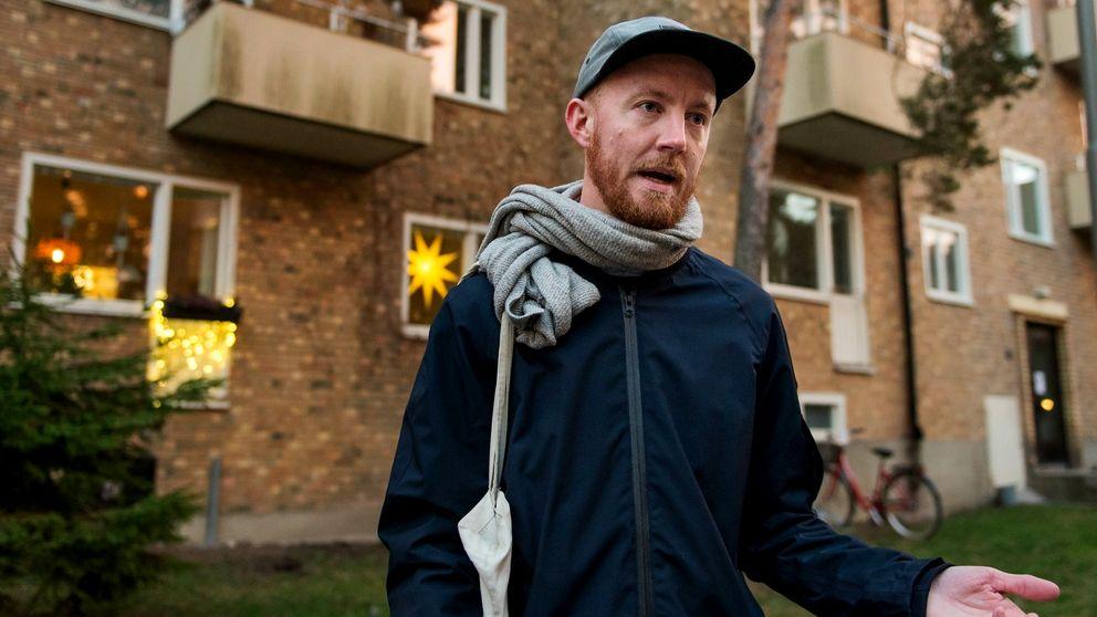 Per Lööf står utanför sitt hem. som är i en tegelbyggnad. Julstjärnor hänger i fönstren. Han bär keps och halsduk.