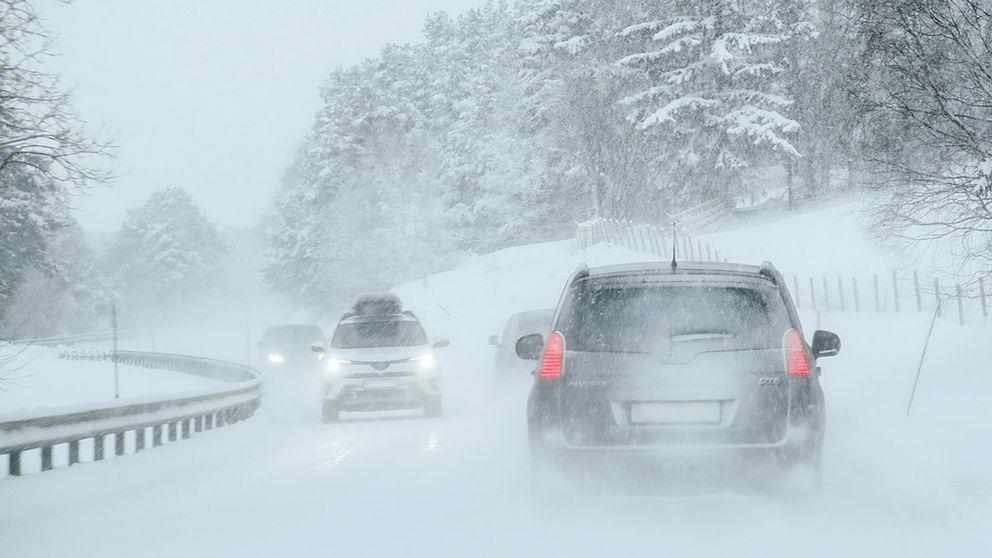 Bilar på en snöig körbana.