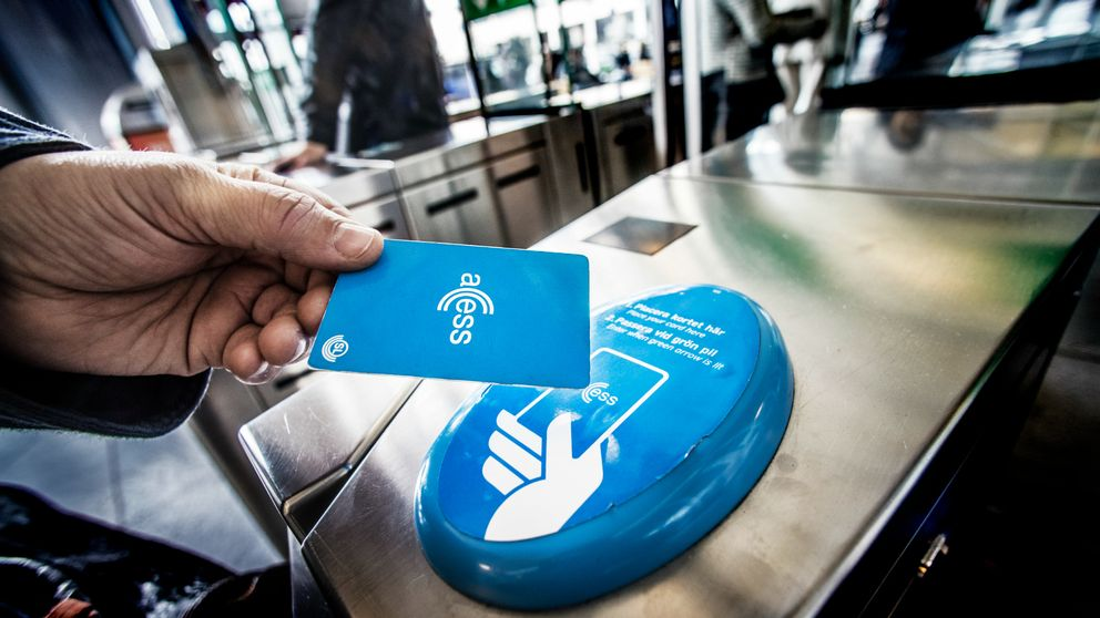 en hand håller ett access-kort över en kortläsare i t-banan