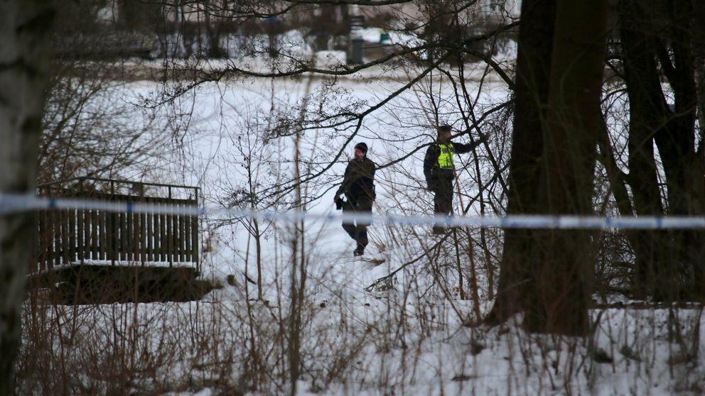 Två poliser söker spår på en snötäckt äng
