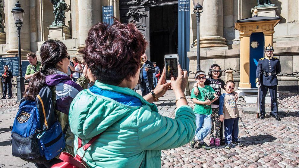 Turister i Stockholm fotograferar utanför Stockholms slott.