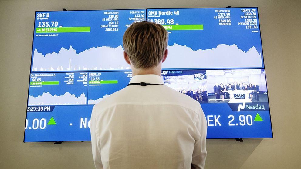 EN man som står framför en skärm som visar börsens utveckling.