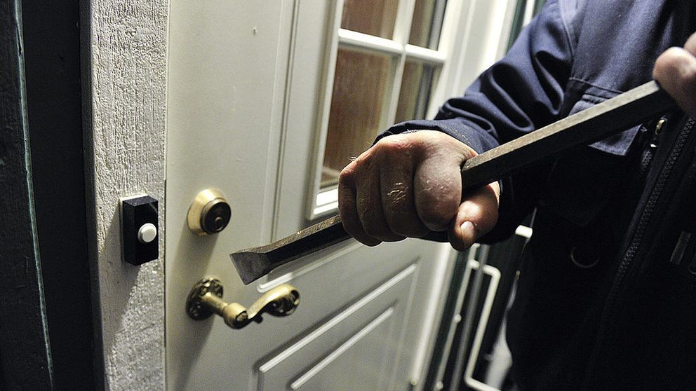 En person som bryter upp en dörr med en kofot.
