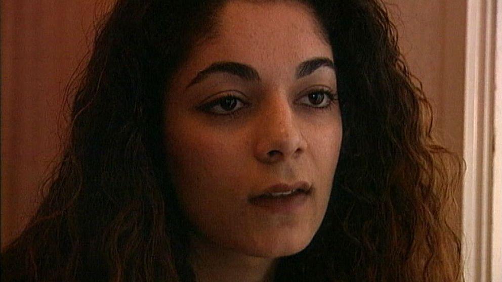 En kvinna med mörka ögon och tjockt mörkt lockigt hår tittat ut ur bild.