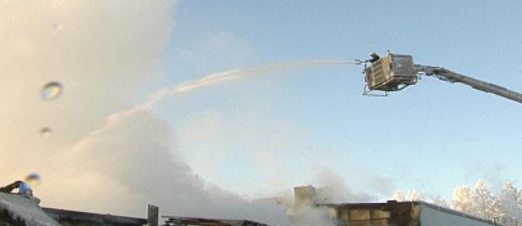 Brandman sprutar vatten från en korghiss