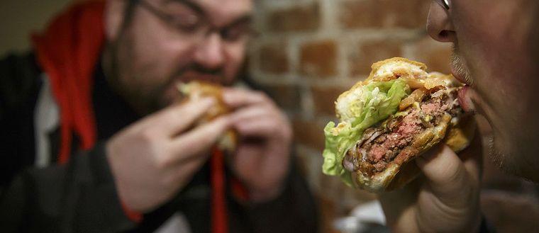 En bild på två personer som sätter i sig hamburgare.