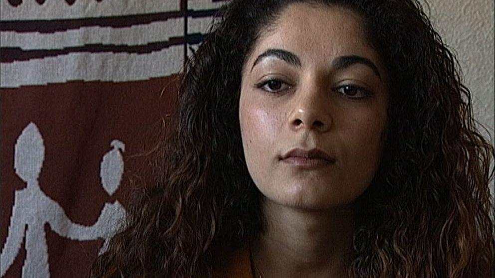 En kvinna med mörkt lockigt hår blickar ut ur bild.