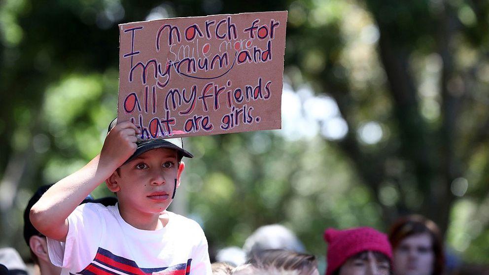 En pojke som håller upp ett plakat.