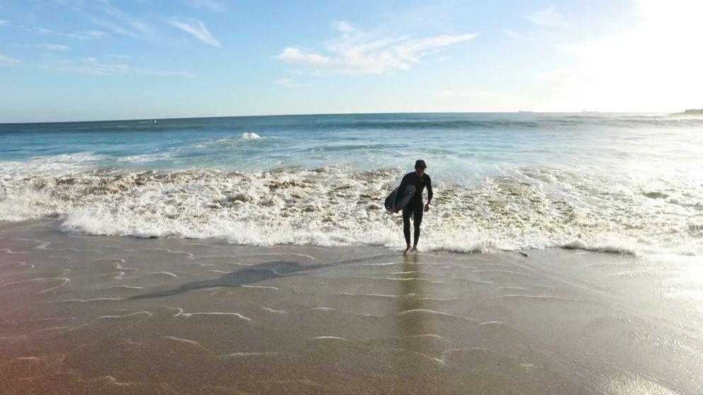 Man går på strand.
