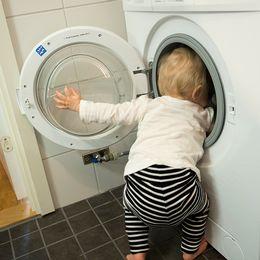 Ett barn står vid en tvättmaskin.