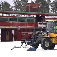En traktor skottar bort snö från en is.