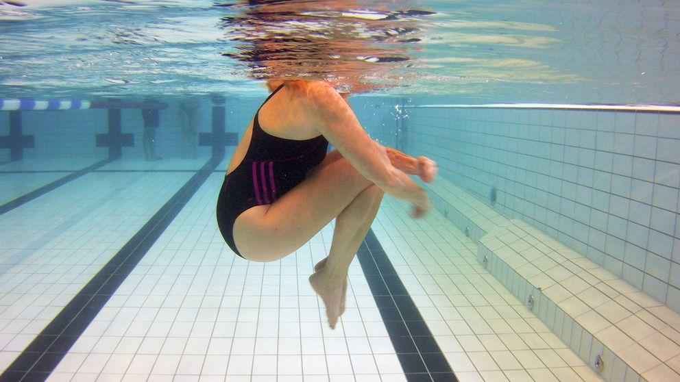 Kvinna i vatten på simhall.