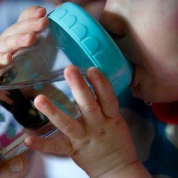 Barn dricker ur en plastmugg.