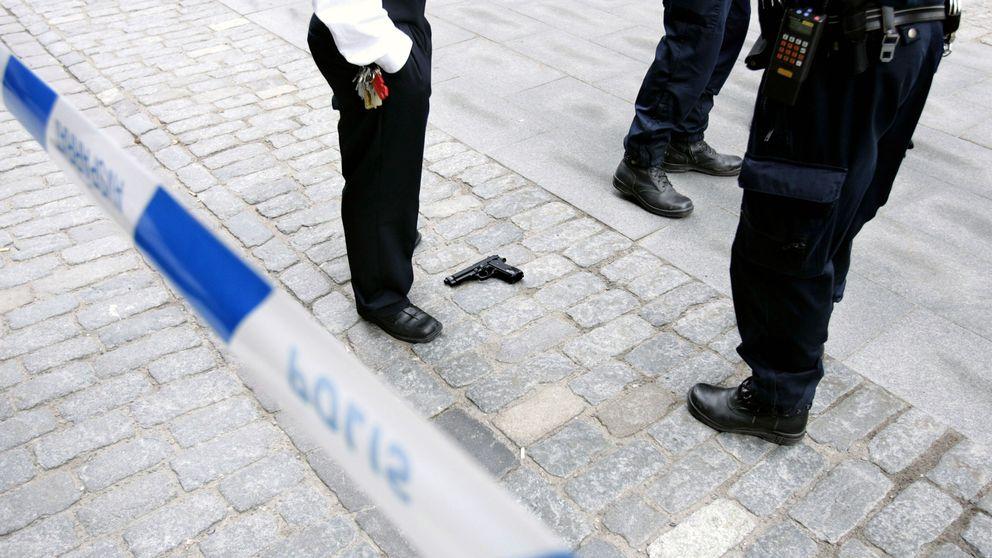 Blå-vitt polisavspärrningsband. Pistol på marken. Man ser vakter/polisers ben.