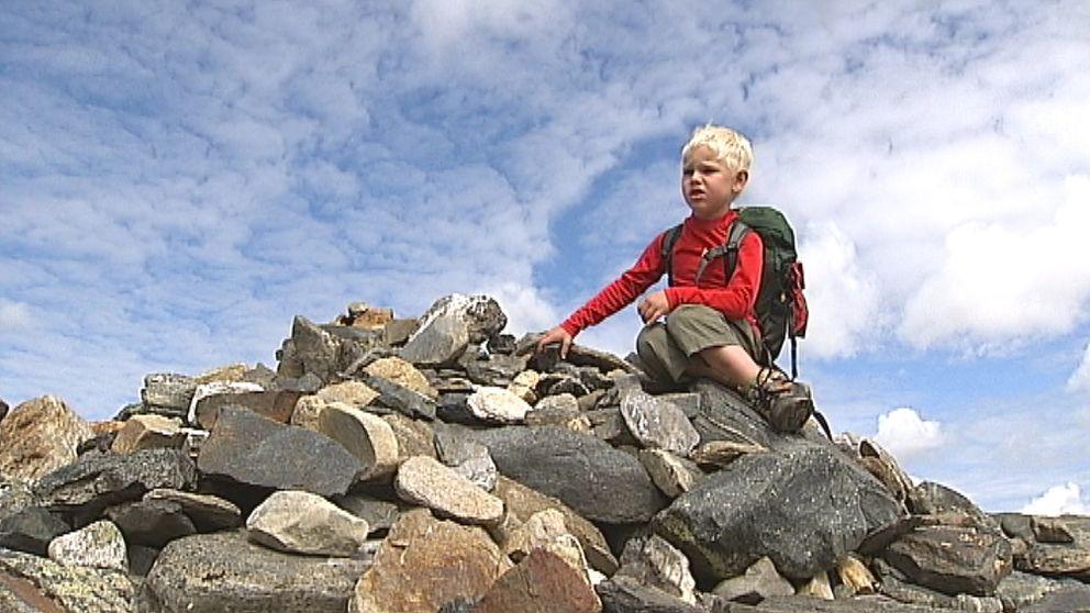 Pojke sitter på stenröse i Fjällen