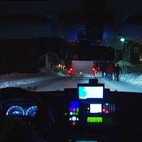 Bild inifrån polisbil ut på snöig väg med trafik och människor.